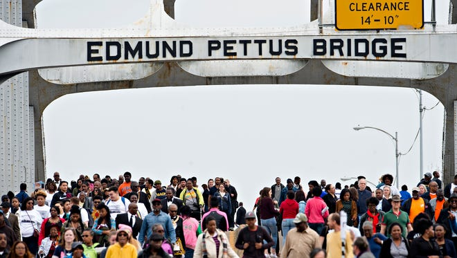 People walk over the Edmund Pettus Bridge towards Selma, Ala., during the 52nd Annual Selma Bridge Crossing Jubilee and Commemoration of Bloody Sunday March in Selma, Ala., on Sunday, March 5, 2017.