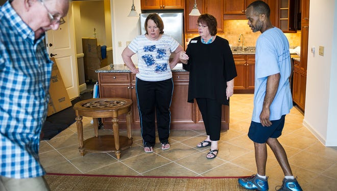 Mary Jo Zeller talks with Debbie Bostock-Herts while Jeff Bostock, left, helps Leonard Hampton move things in to a new room at Arlington of Naples, a senior living community in Naples, Fla., on Thursday, March 2, 2017. Mary Jo Zeller, director of MySolutions at the Arlington, helps families as they prepare to downsize their belongings and move into a smaller apartment.