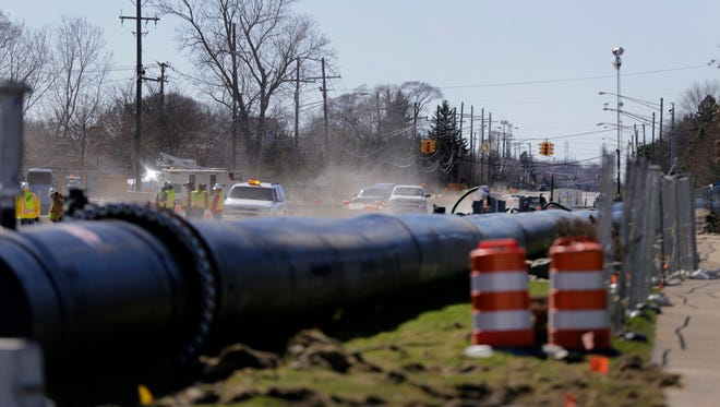 Temporary sewer bypass piping sitting on top of 15 Mile to carry sewage that was installed after a Christmas Eve day sewer collapse and a sinkhole was discovered near Eberlein Drive in Fraser on Friday, April 7, 2017.