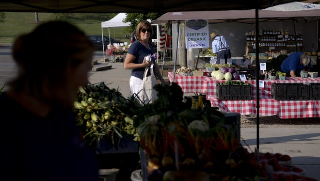 Traci Dudley browses produce in 2016 at the Meridian Township Farmers Market in Okemos.