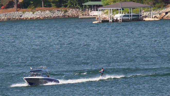 A motorboat pulls a waterskier in Lake Keowee in Seneca, near the shores with boat docks and other recreational boats in Oconee County in April.