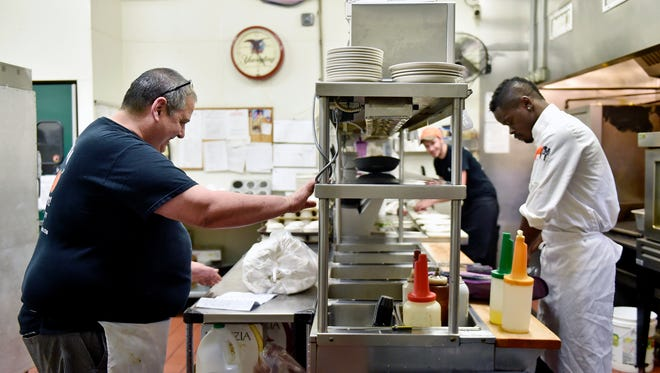 From left, Peach Bottom Inn head chef Jack Lopez reviews paperwork as cook Matthew Klein and new sous chef Artis Bellamy prepare food Thursday, June 1, 2017. Exelon's Peach Bottom Atomic Power Station nuclear power plant drives much of the surrounding area's economy, especially in the borough of Delta in southeast York County. Lopez said much of the restaurant's business relies on longtime and temporary employees of the Peach Bottom power plant, and that the restaurant and adjoining motel would be adversely affected if the plant were to shut down.