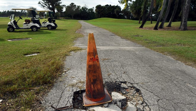 An orange cone alerts golfers of a severe pot hole Wednesday, in late 2016, at the Martin County Golf Course in Stuart.