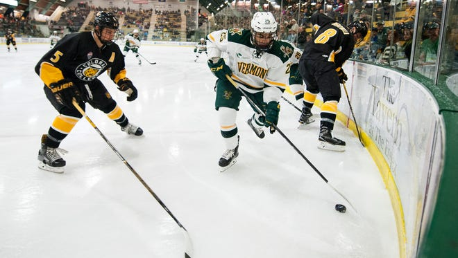 Vermont forward Matt Alvaro (25) plays the puck in the corner during the men's hockey game between the Colorado College Tigers and the Vermont Catamounts at Gutterson Fieldhouse  last month.