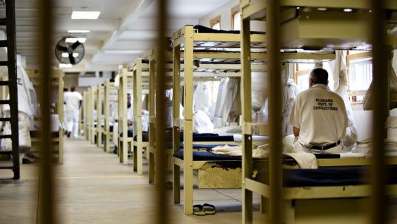An inmate sits on his bed at Draper Correction Facility