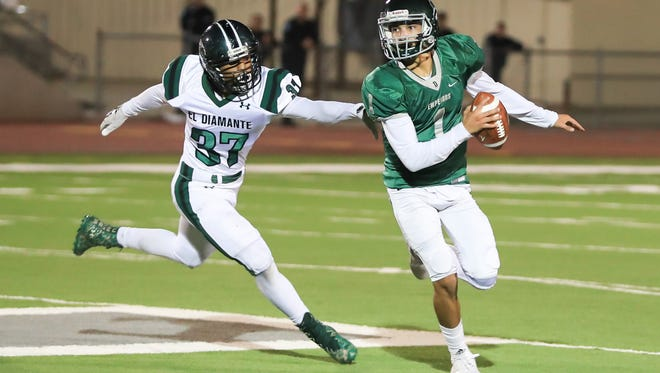 Dinuba's QB Josh Magana (1) scrambles away from El Diamante's (37) Diego Pena in a Central Section Division II Semifinal high school football game at Claud Hebert Field on Nov 17, 2017.