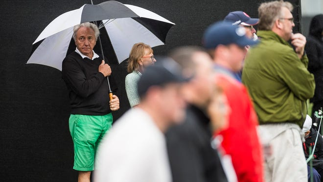 People shield themselves from the rain during the second round of the QBE Shootout at Tiburón Gulf Club in Naples, Fla., on Saturday, Dec. 9, 2017.