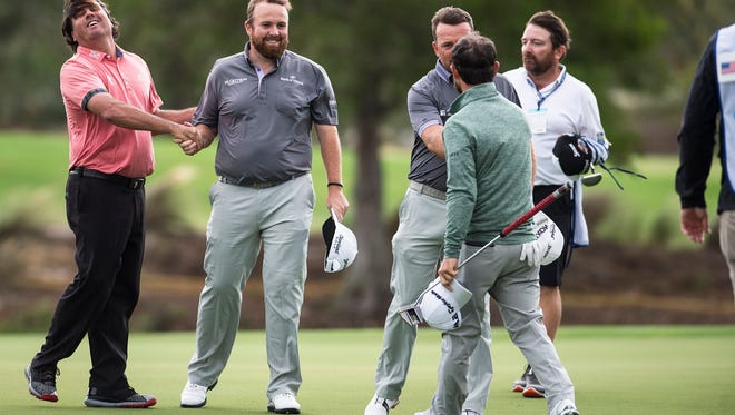 Shane Lowry (left) and Graeme McDowell shake hands with Pat Perez and Brian Harman at the 18th hole following the second round of the QBE Shootout at Tiburón Golf Club in Naples on Saturday. Lowry and McDowell fired an 8-under 64 and are tied with Steve Stricker and Sean O'Hair for the lead.