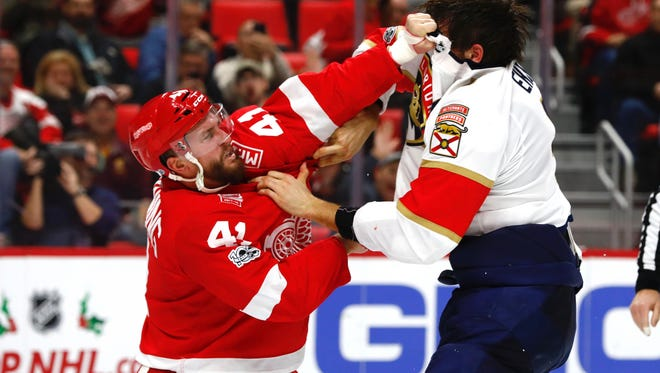 Red Wings right wing Luke Glendening (41) and Panthers defenseman Aaron Ekblad (5) fight in the second period of the Wings' 2-1 overtime loss on Monday, Dec. 11, 2017, at Little Caesars Arena.