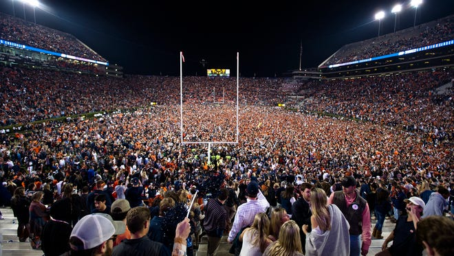 Auburn fans storm the field after the Iron Bowl NCAA football game between Auburn and Alabama on Saturday, Nov. 25, 2017, in Auburn, Ala. Auburn defeated Alabama 26-14.