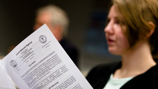 A attendee of the Alabama Medicaid Public Forum reads