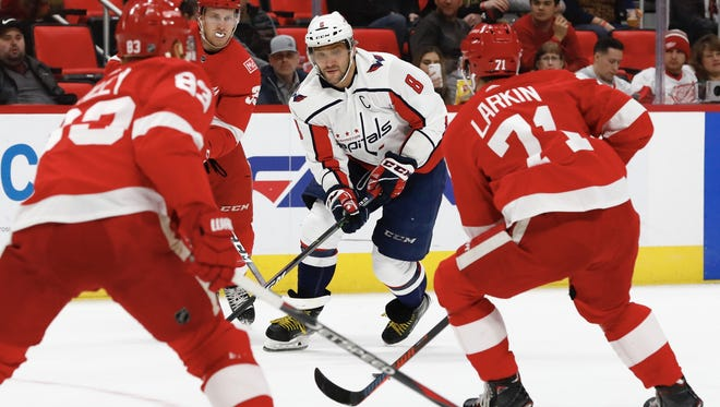 Capitals left wing Alex Ovechkin (8) skates with the puck defended by Red Wings defenseman Trevor Daley (83) and center Dylan Larkin (71) in the first period on Thursday, March 22, 2018, at Little Caesars Arena.
