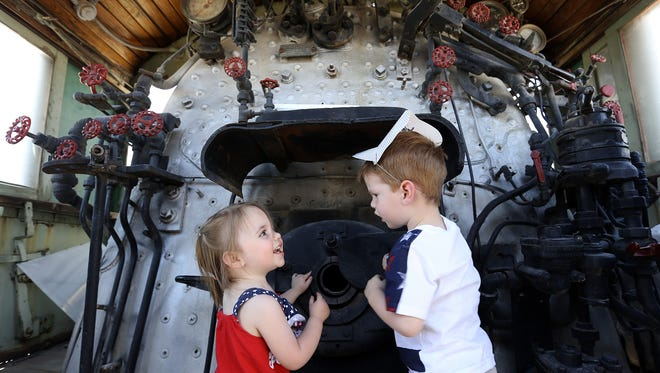 Catherine Bell, 1, tells her brother James Bell, 2, she saw an alligator in the firebox of a 1904 locomotive Saturday during the El Paso Train Show at Freeport McMoRan Park, 850 Hawkins Blvd. Also on display were a 1929 caboose and antique railroad items. The event continued through Sunday.