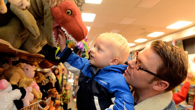 Treyson Strunk, age 2, enjoys the stuffed animals at Amazing Toys while shopping with his dad, Shawn. Generations of Great Falls kids and kids at heart will miss Amazing Toys as the longtime Great Falls fixture goes out of business this summer.