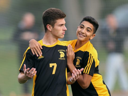Athena's CJ Takatch (7) is congratulated after his goal by teammate Othman Belseine (2).