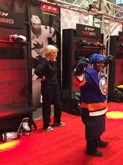 Stemarion Midgett, 11, tries on a hockey uniform at
