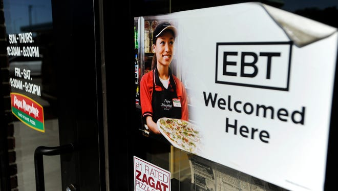 A sign tells customers that an Electronic Benefits Transfer (EBT) card, the debit card for food stamps, can be used at the store.