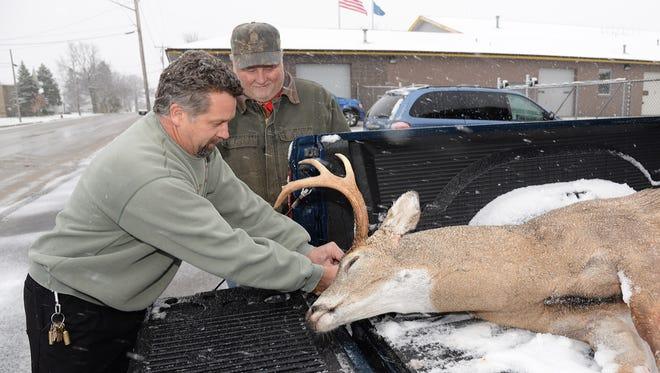 Lee Simonar, left, owner of Lee's Sports in Luxemburg, registers a buck arrowed Nov. 9 by local bowhunter Dana Lemens.