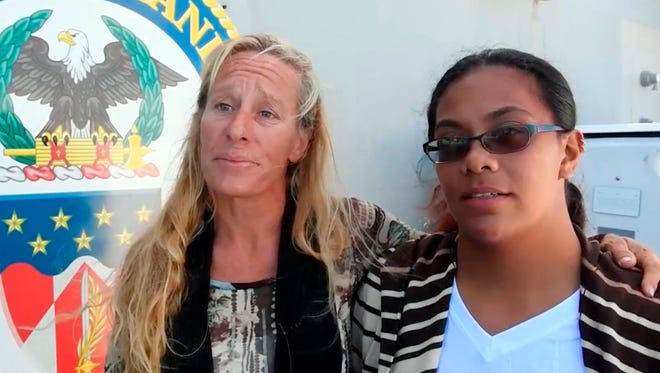 In this Wednesday, Oct. 25, 2017 frame from video provided by the U.S. Navy, Jennifer Appel, left, and Tasha Fuiava, who with their dogs were rescued after being lost at sea for several months while trying to sail from Hawaii to Tahiti, are interviewed aboard the USS Ashland in the South Pacific Ocean.