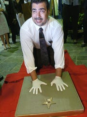 FILE PHOTO: Eugene Mosley smiles as he presses his hand imprints into a block of cement while being inducted into the Shreveport Walk of Stars, March 14, 2008, at the Chamber of Commerce Plaza.