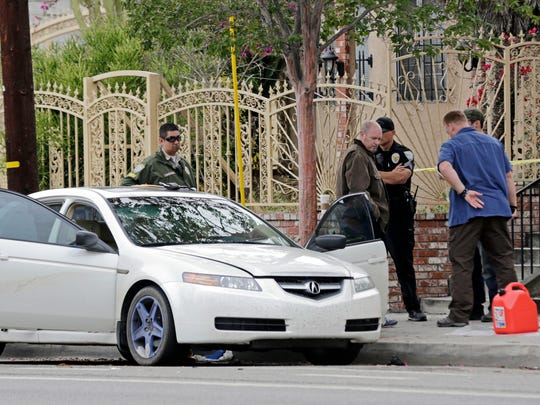 Investigators view items removed from a car, left, after a heavily armed man was arrested in Santa Monica, Calif., early Sunday, June 12, 2016.