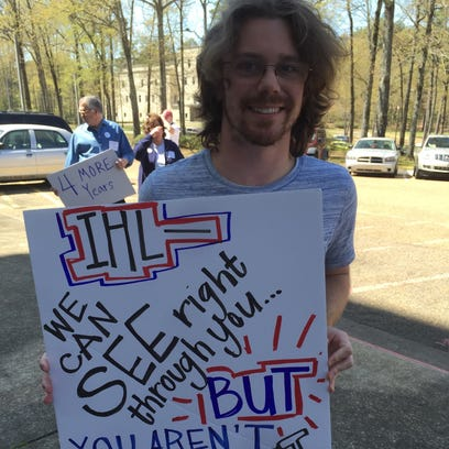 Brian Spurlock of Jackson holds a sign during a rally