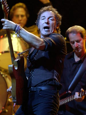 Bruce Springsteen, left, performs with the E Street Band at Dodger Stadium in Los Angeles, on Aug. 17, 2003. Behind Springsteen are E Street Band members Max Weinberg, left, and Garry Tallent.