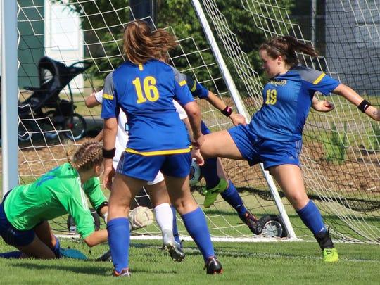Marian's sophomore defender Anna Leonard (19) kicks