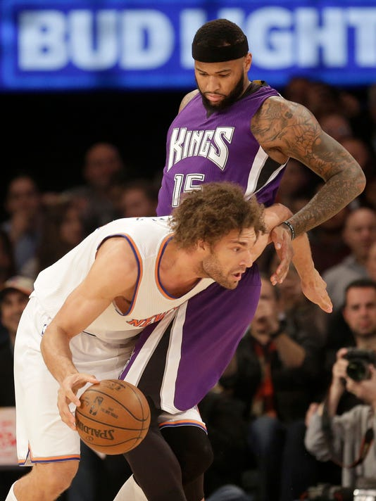 New York Knicks' Robin Lopez, left, pushes past Sacramento Kings' DeMarcus Cousins during the first half of the NBA basketball game, Sunday, March 20, 2016 in New York. (AP Photo/Seth Wenig)