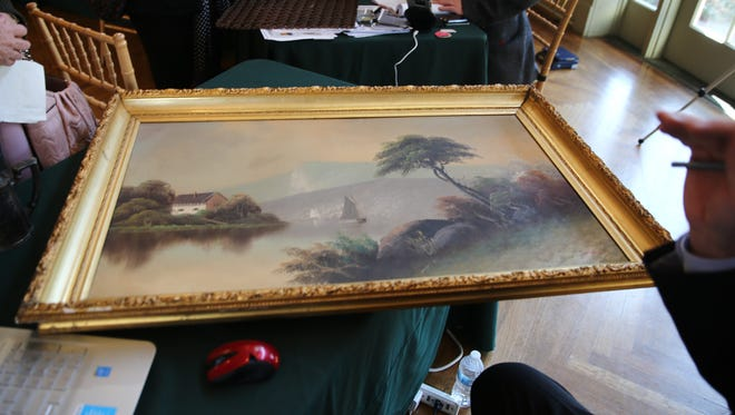 A painting of a river from the late 1800s sits on a table Sunday. Jackie Williams said her late father left her the painting and told her it was worth more than his house. It wasn't.