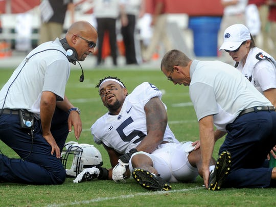 """Head coach James Franklin, left, helps tend to an injured Nyeem Wartman-White during Penn State's loss to Temple in 2015. Wartman-White didn't give up football after this and another injury. He had been tested tough before those, too. Especially as a teenager, after his older brother Markel, his idol, was convicted of robbing a store in Philadelphia and sent to prison. """"He wanted to quit (football). He said he was tired of it, didn't want to play anymore,"""" Markel White said. """"I'm like, 'Play for you. Don't do it for me, do it for yourself.'"""""""