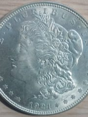 The coin is a 1921 Morgan Silver dollar, which is the