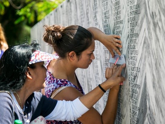 Virginia Hurley, left, helps her daughter Loren take a rubbing of her dad's name on Monday after the Memorial Day ceremony at Coral Ridge Cemetery in Cape Coral. Leroy Hurley was an Army veteran.