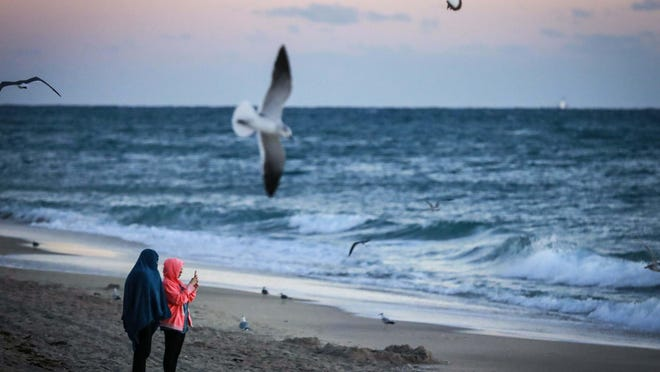 Beachgoers are bundled up for warmth Sunday morning in Lake Worth Beach. Temperatures dropped overnight Saturday and were in the upper 50s by sunrise.