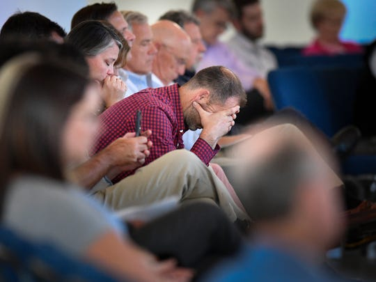 Guests pray during a vigil at Woodmont Hills Church
