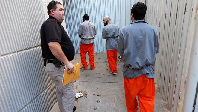 Corporal Darryl Adkins, left, escorts prisoners into the Greene County Jail in Springfield from a Department of Corrections facility on Wednesday, Jan. 13, 2016.