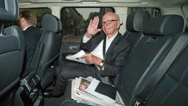 Media mogul Rupert Murdoch waves to photographers as he is driven away from News U.K. headquarters in London on June 26.