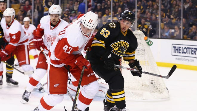 Red Wings defenseman Alexey Marchenko defends the Bruins' Brad Marchand during the first period of the Wings' loss Saturday in Boston.