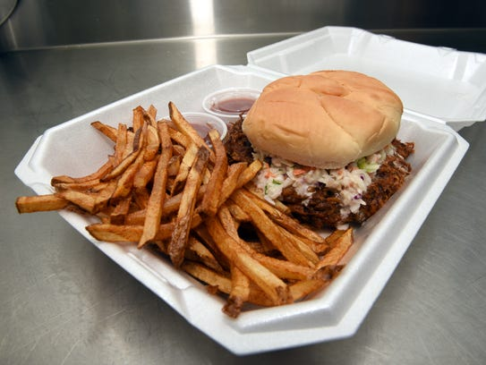 A pulled pork sandwich with homemade coleslaw and a