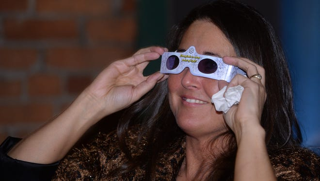 Leann Wiford tries on a pair of party glasses during the InCONCERT 2015 New Year's Eve Celebration in Richmond, which helps out local non-profits.