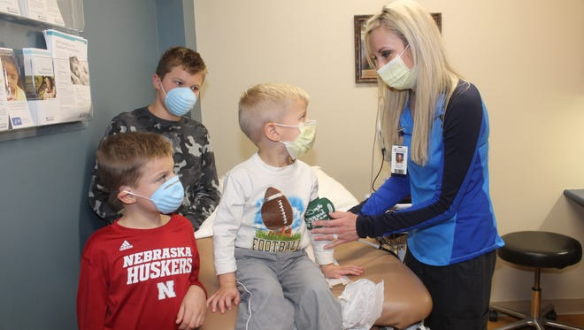 For Nathan and Shannon Johnson of Oskaloosa, this flu season has hit their household hard. All but one of their children is sick. Shown at the Mahaska Health Partnership Walk-In Clinic getting his vitals taken by Nurse Erika Sieren, is 3-year-old Jaxon. They are surrounded by his brothers, Caden, 11 and Colin, 8, who are also sick.