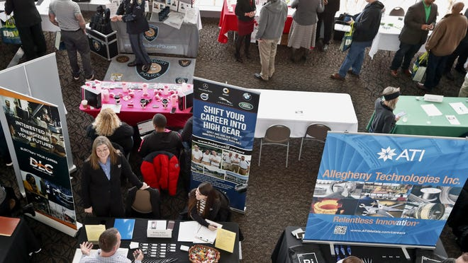 In this March 7, 2019, photo visitors to the Pittsburgh veterans job fair meet with recruiters at Heinz Field in Pittsburgh.