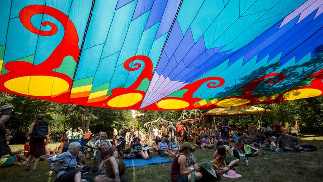 Fair attendees seek shade under a rainbow canopy on the first day of the 50th annual Oregon Country Fair on July 12, 2019. [Dana Sparks/The Register-Guard file] - registerguard.com