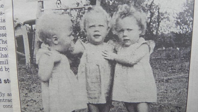 Three big dolls: Jane, Judy and Joan at age 2. In the background is the well where water was drawn to wash the triplet-sized laundry.