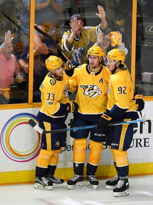 Nashville Predators left wing Viktor Arvidsson (33) and center Ryan Johansen (92) celebrate with left wing Filip Forsberg (9) after his game-winning goal in the closing minutes of the third period of the home opener at Bridgestone Arena in Nashville, Tenn., Tuesday, Oct. 10, 2017.