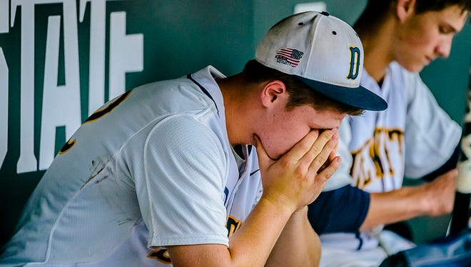 DeWitt pitcher Michael Stygles sits on the bench as his teammates pack up after their 4-3 Division 2 state semifinal loss to Holland Christian Thursday June 16, 2016 McLane Stadium on the MSU campus in East Lansing.  Stygles gave up the game winning run with 2 outs in the top of the 7th inning and failed to reach base on his at-bat in the bottom of the 7th.