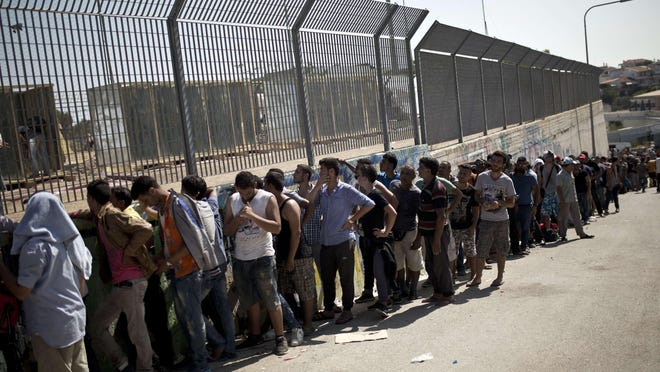 Migrants wait to complete their registration procedure by the police at the new registration center held in a stadium on the Greek island of Lesbos on Sept. 8.