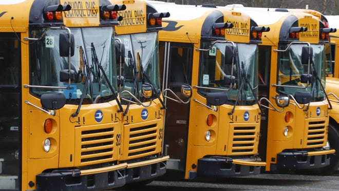 Parked school buses are lined up while they are idled during school closings due to the COVID-19 pandemic.