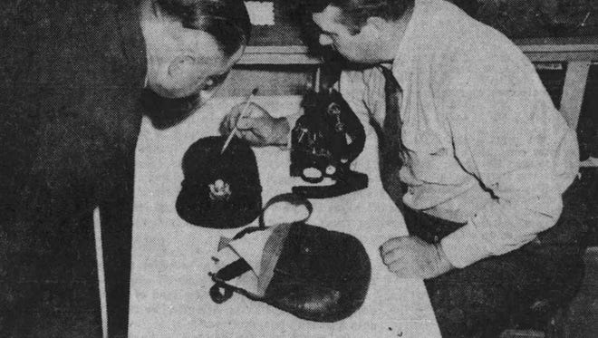 Photo shows shows Sioux Falls Police Chief Fred Searls and identification officer Herman Ostlund investigating clues before they were sent to the FBI.