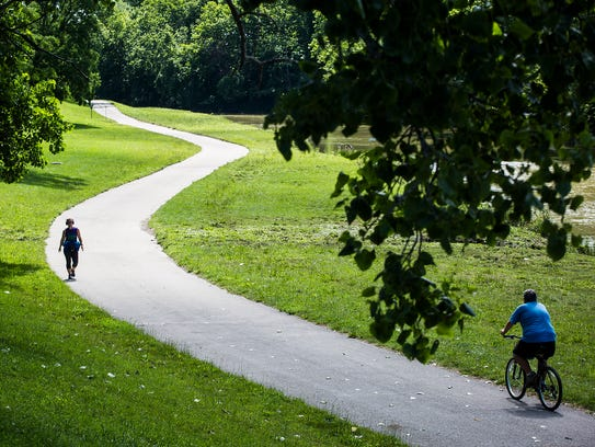 Walkers and bikers travel along the White River Greenway